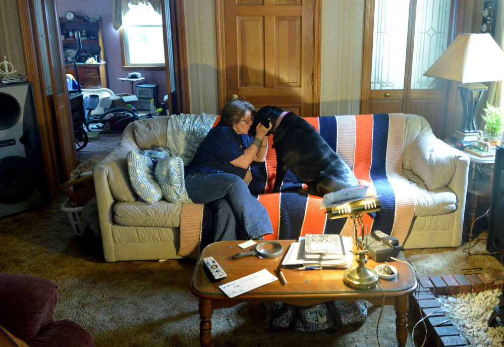 Eva St. Jean is comforted by her dog, Jasmine, as she talks about the struggle to find Waterville rental housing that will allow her to live the 80-pound black Lab mix.