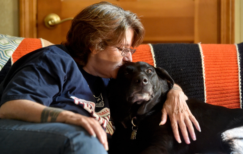 Eva St. Jean is comforted by her dog, Jasmine, as she talks about the struggle to find housing in Waterville that will allow her to live with the 80-pound black Lab mix. Pet owners say the city isn't pet-friendly to those looking for rental housing. St. Jean is staying with a friend in Clinton as she looks for somewhere to live.