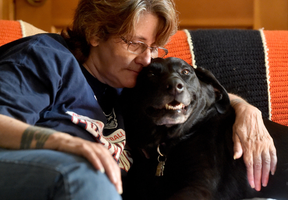 Eva St. Jean is comforted by her dog, Jasmine, as she talks about the struggle to find Waterville housing that will allow her to live with the 80-pound black Lab mix.