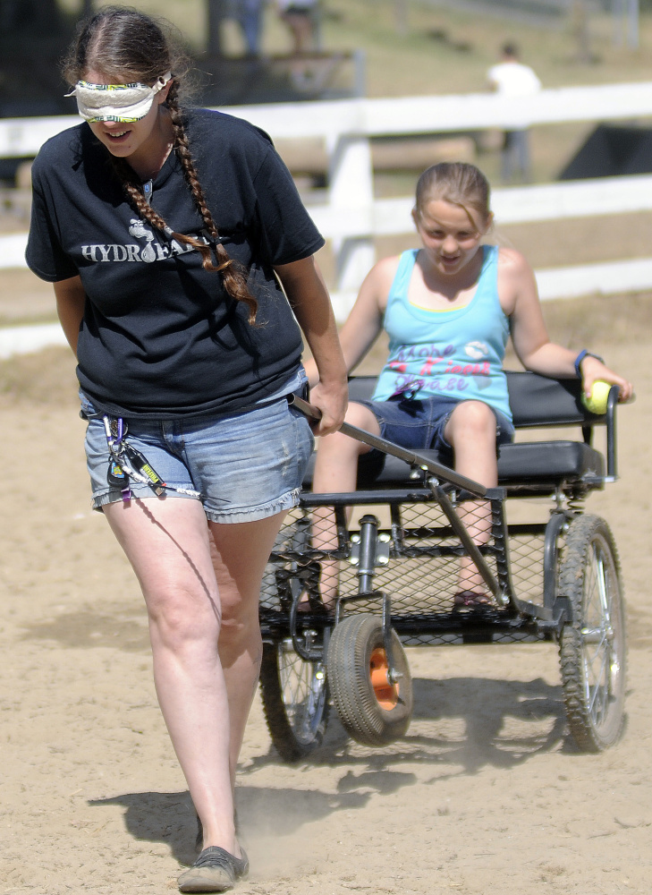 Jennifer Morrison follows instructions from her daughter, Chianna, 10, while competing in the Back Seat Driver Contest at the Monmouth Fair on Sunday.