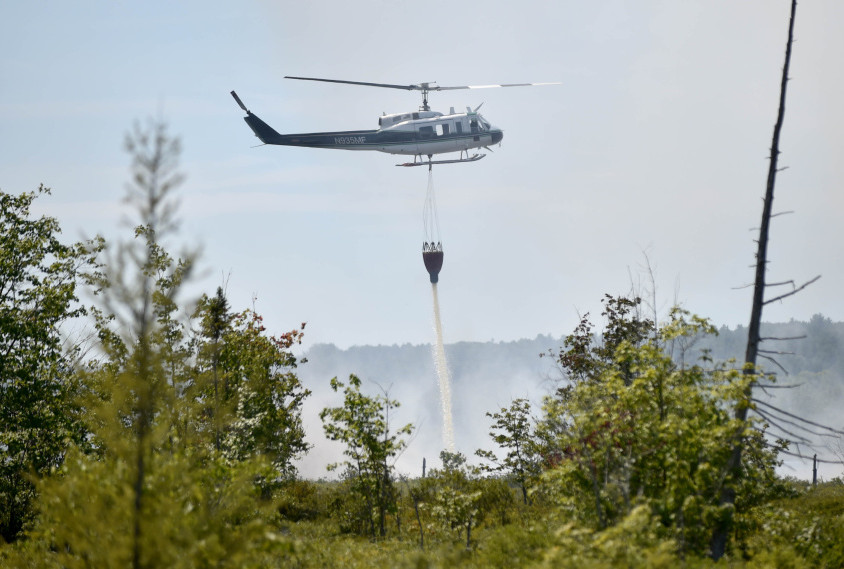 A forest service helicopter attacks a wildfire Tuesday near Mud Pond in China. The fire burned about 2 acres near the Winslow-China town boundary over five hours. Firefighters were back at the site Wednesday to monitor hot spots.