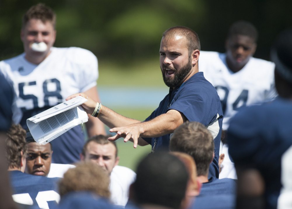 New University of Maine football head coach Joe Harasymiak talks with his team after practice Monday in Orono.