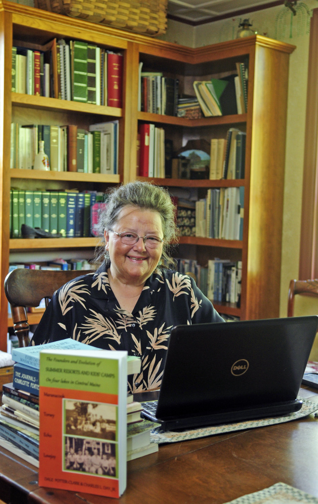 Dale Potter-Clark poses for a portrait Wednesday with her recently published book at her Vassalboro home.
