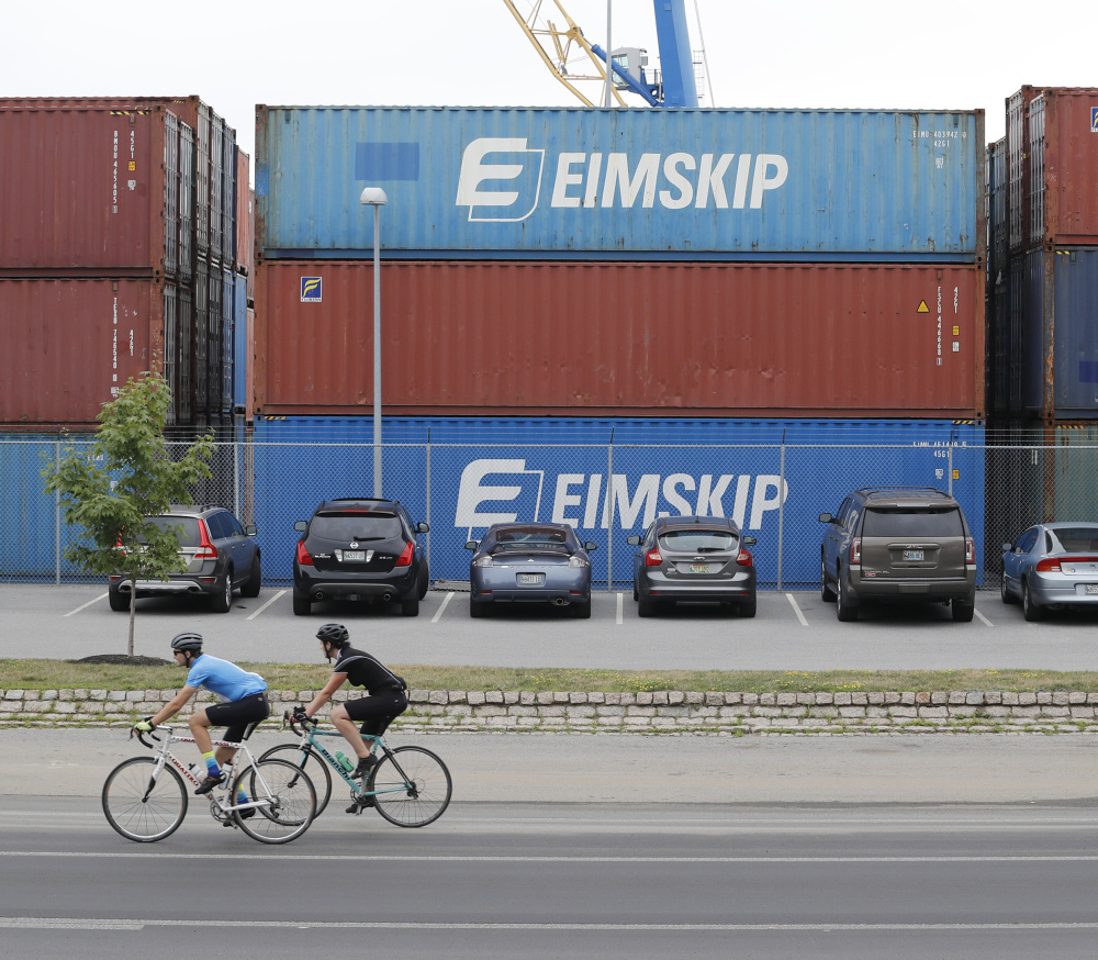 Cyclists pass shipping containers Monday at the International Marine Terminal. Iceland's Eimskip uses some converted containers as year-round office space at the terminal.