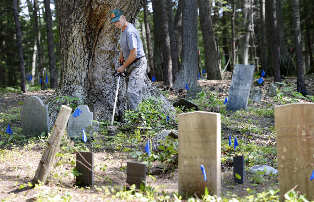 Ken Mann tends to graves in Mann Cemetery last week. He and other Freeport residents want to restore public access to the 18th-century graveyard across land owned by L.L. Bean.
