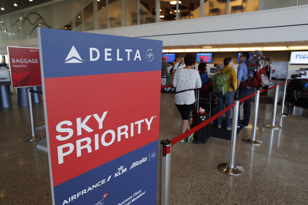 Passengers wait in line to check in for Delta flights Monday at the Portland International Jetport. Delta faced delays around the country because of a system problem in Atlanta.