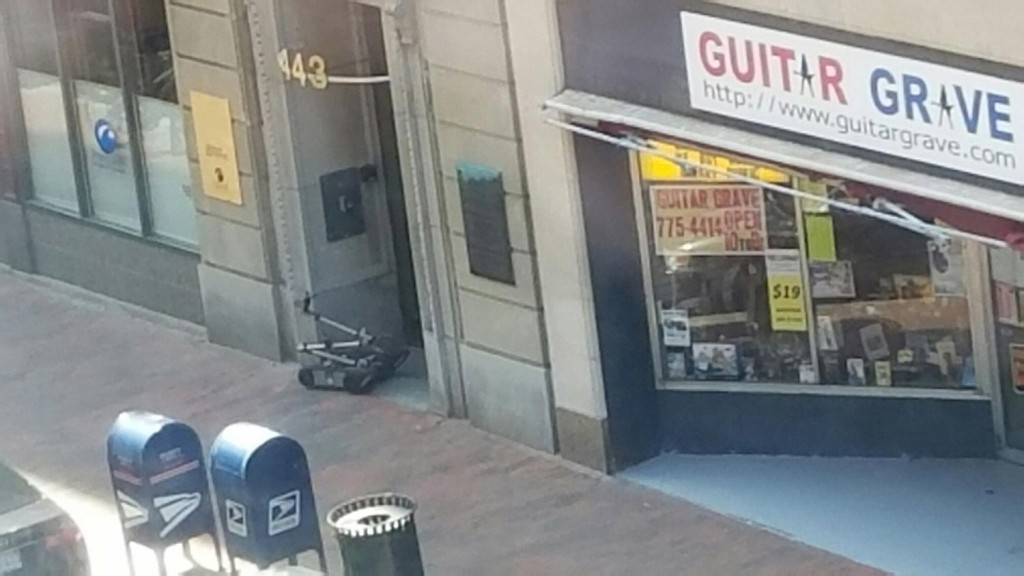 The Portland Police Department bomb squad deployed a robot, seen in the doorway of 443 Congress St., to investigate a suspicious package Tuesday.