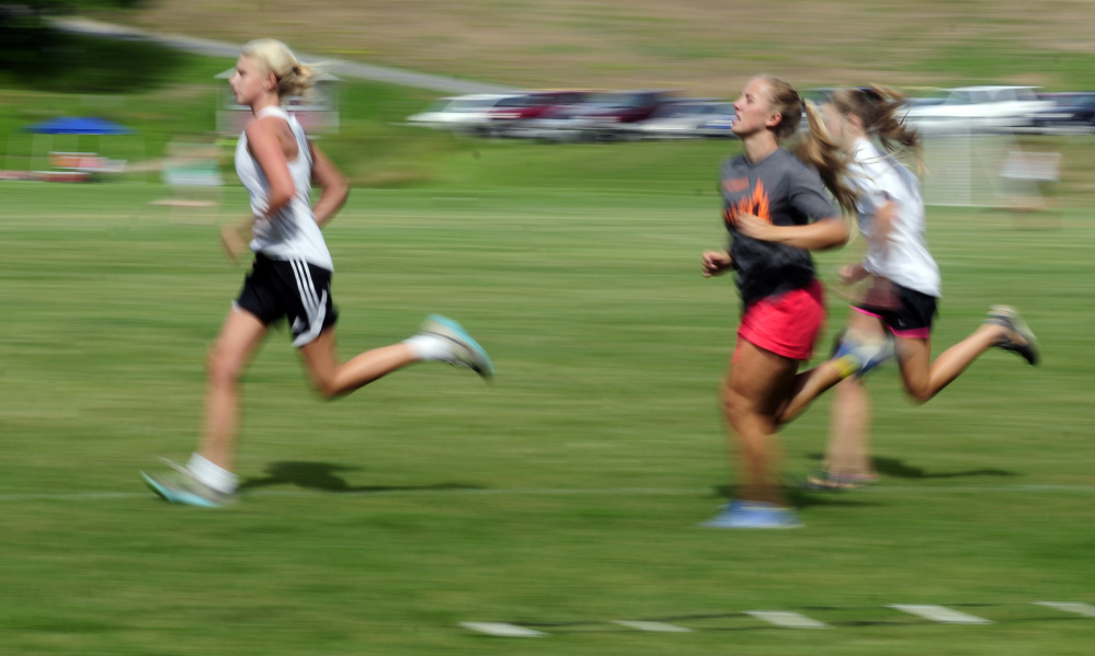Staff photo by Joe Phelan   Monmouth girls soccer players run laps around the field for conditioning at the end of an Aug. 16 preseason practice. The Mustangs are off to another strong start.