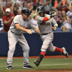 Boston Red Sox third base coach Brian Butterfield, left, congratulates Dustin Pedroia, who circles the bases after hitting a grand slam off Tampa Bay reliever Danny Farquhar during the seventh inning Saturday in St. Petersburg, Florida.