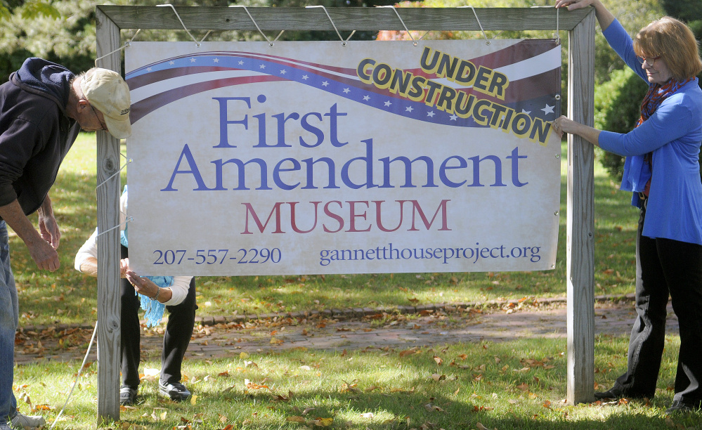 Genie Gannett, right, hangs a sign Monday for the First Amendment Museum in front of the Gannett House in Augusta with Denis Thoet, left, and Susan Gross.