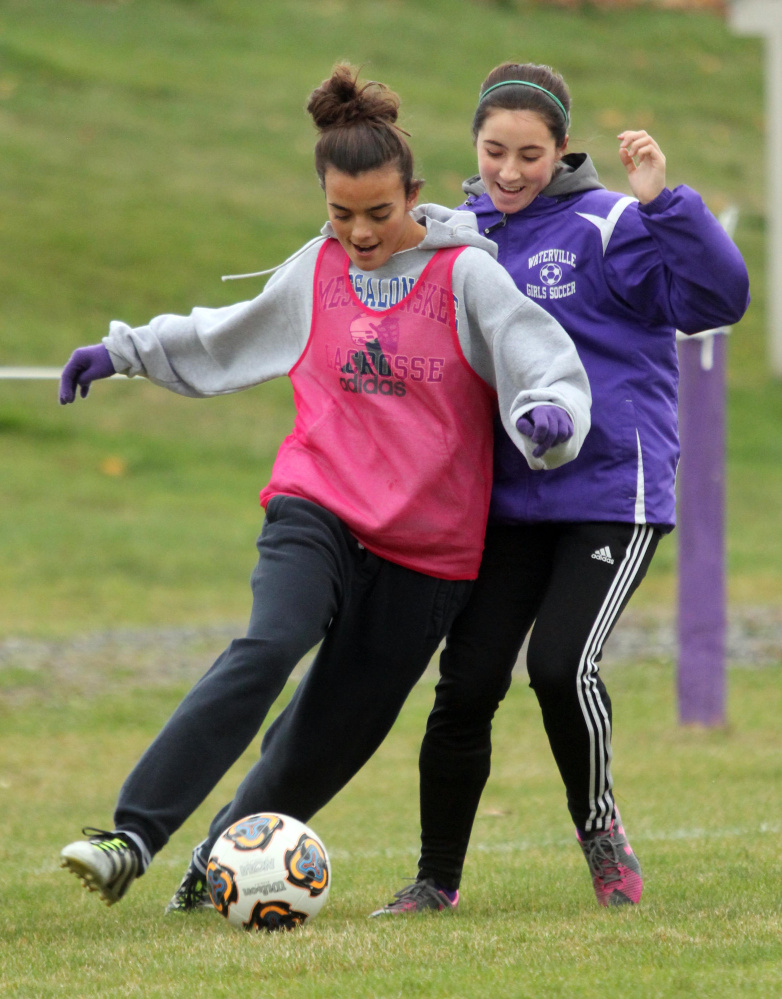 Waterville Senior High School's Jordan Jabar tries to keep the ball from Lily Foster during practice on Monday.