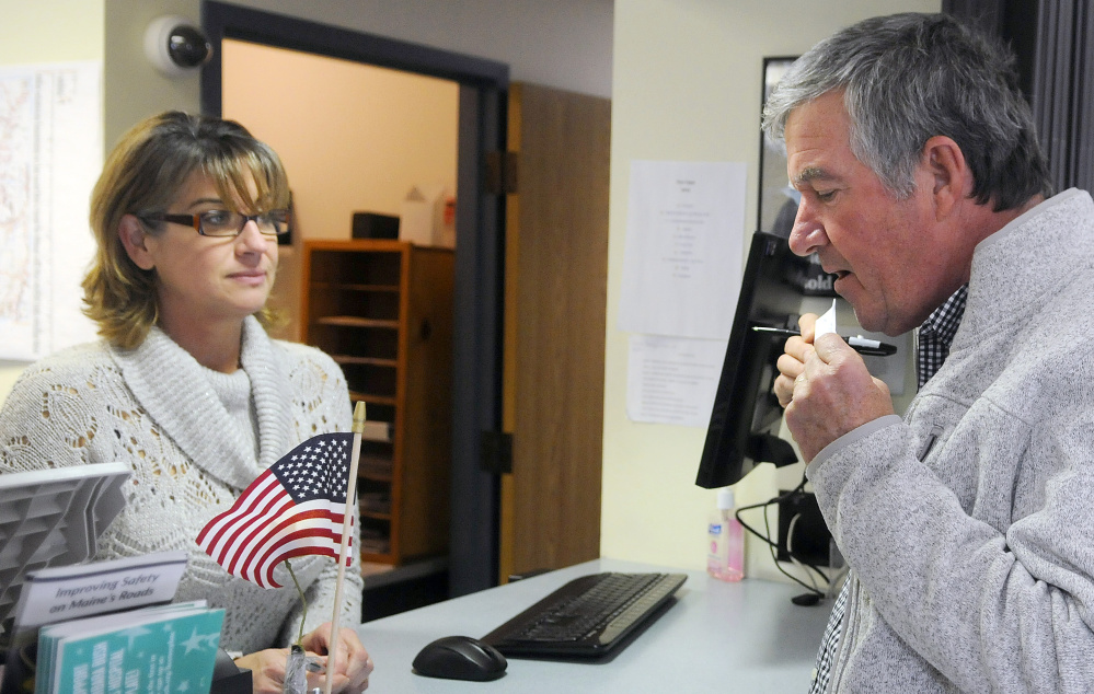 Steve Kalenda seals a ballot Tuesday before handing it over to Monmouth Deputy Town Clerk Kim Dalton. Towns are reporting a higher-than-normal early voting trend.
