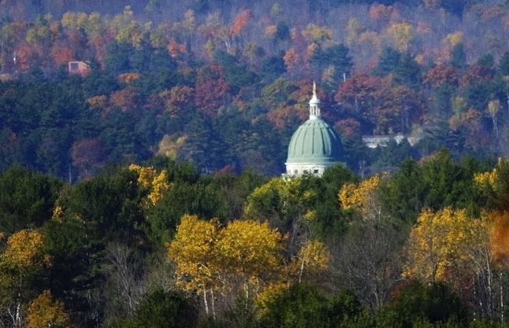 Fall foliage dots Howard Hill rising behind the State House from Route 17 in Augusta. The Land for Maine's Future Board voted Tuesday to reduce the state's contribution toward purchasing the 164-acre tract for public use.