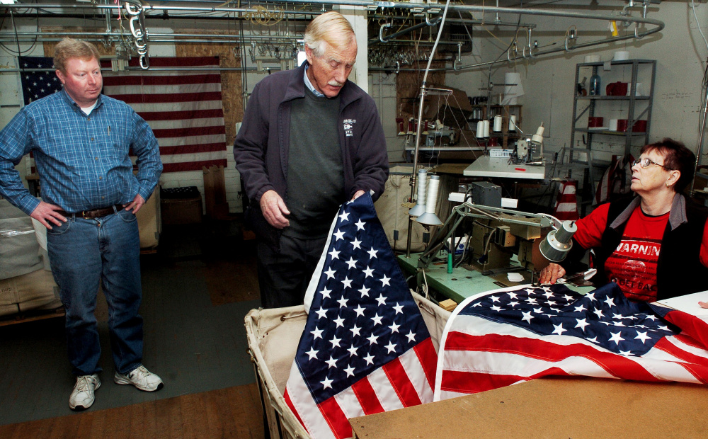 U.S. Sen. Angus King, I-Maine, center, examines an American flag sewn by Maine Stitching Specialties employee Charlene Goodrich as owner Bill Swain conducts a tour of the Skowhegan company on Tuesday.