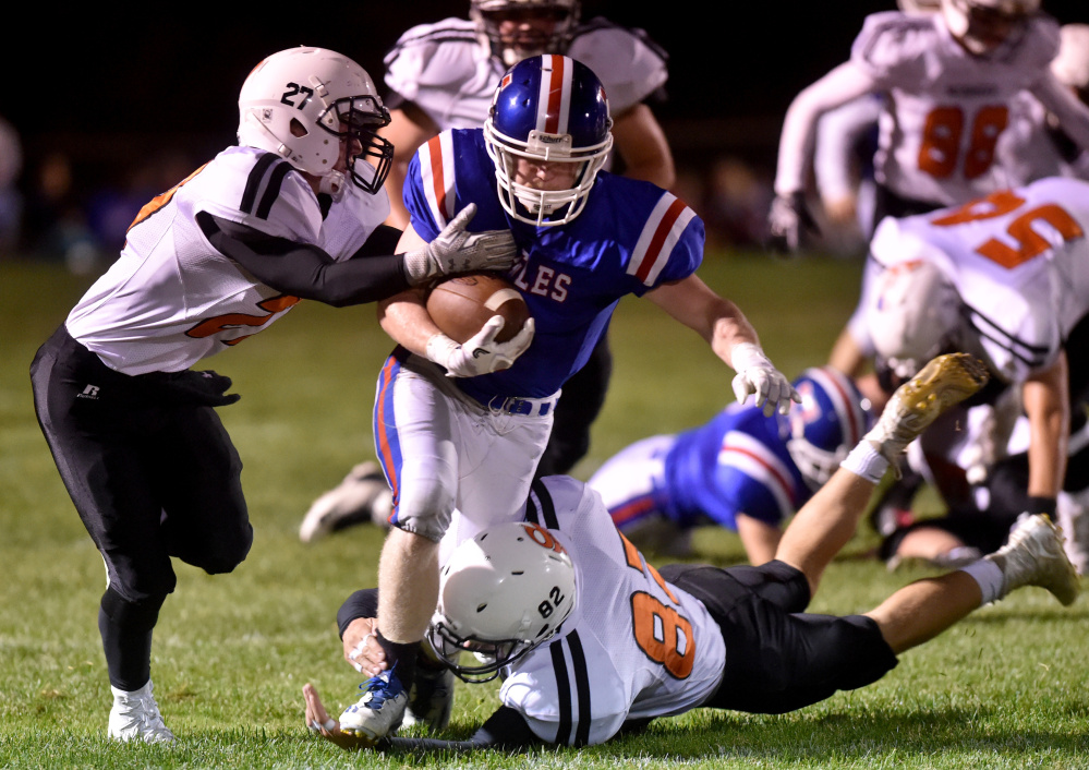 Messalonskee running back Austin Pelletier, center, breaks away from Skowhegan defenders Cooper Holland, left, and Garrett McSweeney during an Oct. 7 game.