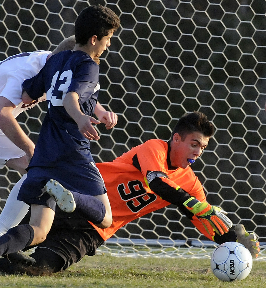 Richmond goalie Zach Small covers a shot from Greenville's Chris Caiazzo during the Class D South regional final Wednesday in Richmond.