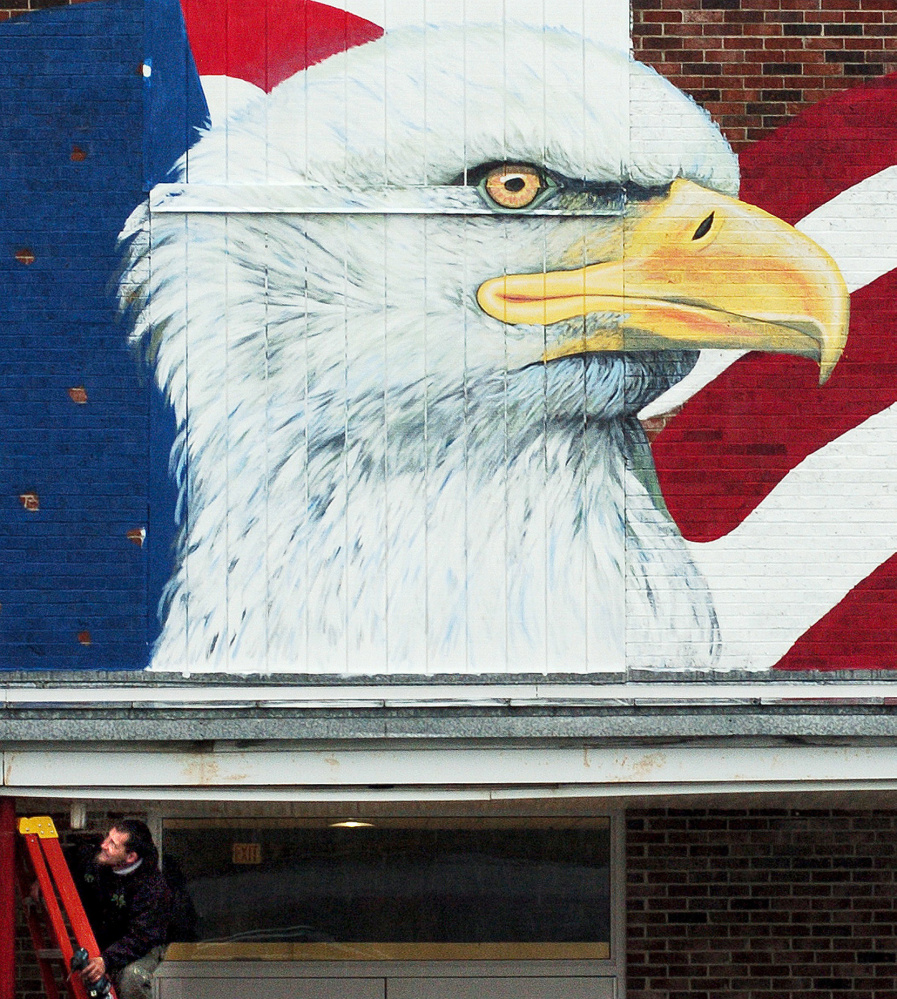 Worker Gary Page adjusts a drain for water Thursday on the canopy of the Skowhegan Village plaza building where a large mural showing an American flag and an eagle is being painted outside the Maine Veterans Museum that is under construction.