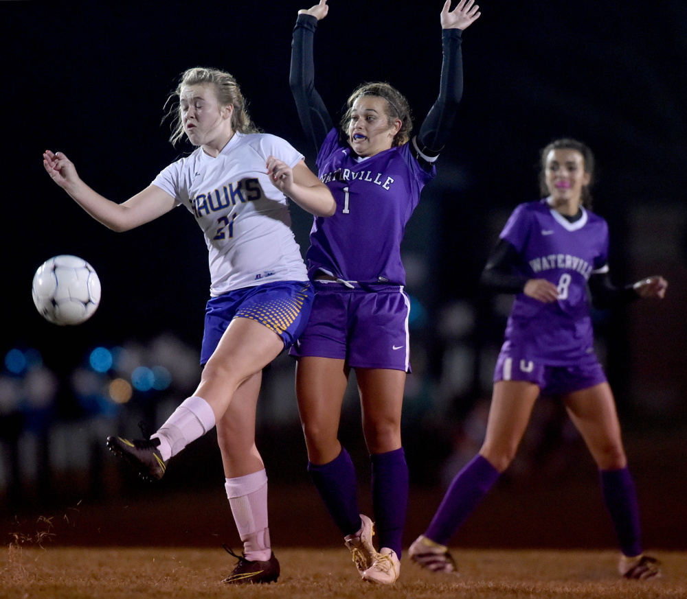 Staff photo by Michael G. Seamans Waterville's Mackenzie St. Pierre, right, defends Hermon's Maddisyn Curtis (21) during the Class B North championship game Wednesday night in Hermon.