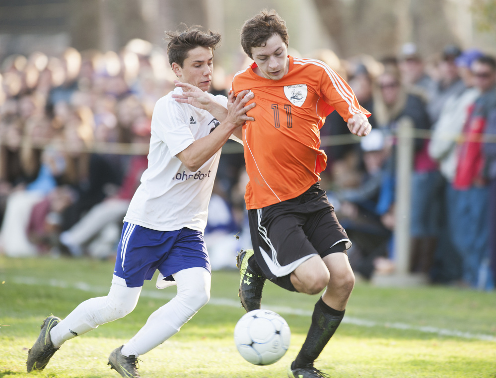 Winslow's Isaac Lambrecht is shoved by John Bapst's Brady Chadwick during a scramble to control the ball in the second half of the Class B North final Wednesday in Orono.