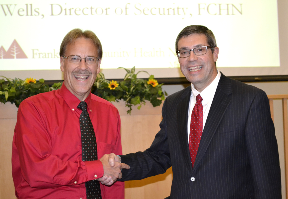 Roger Wells, left, director of security, receives the Franklin Community Health Leadership Award from board chairman Clinton Boothby.