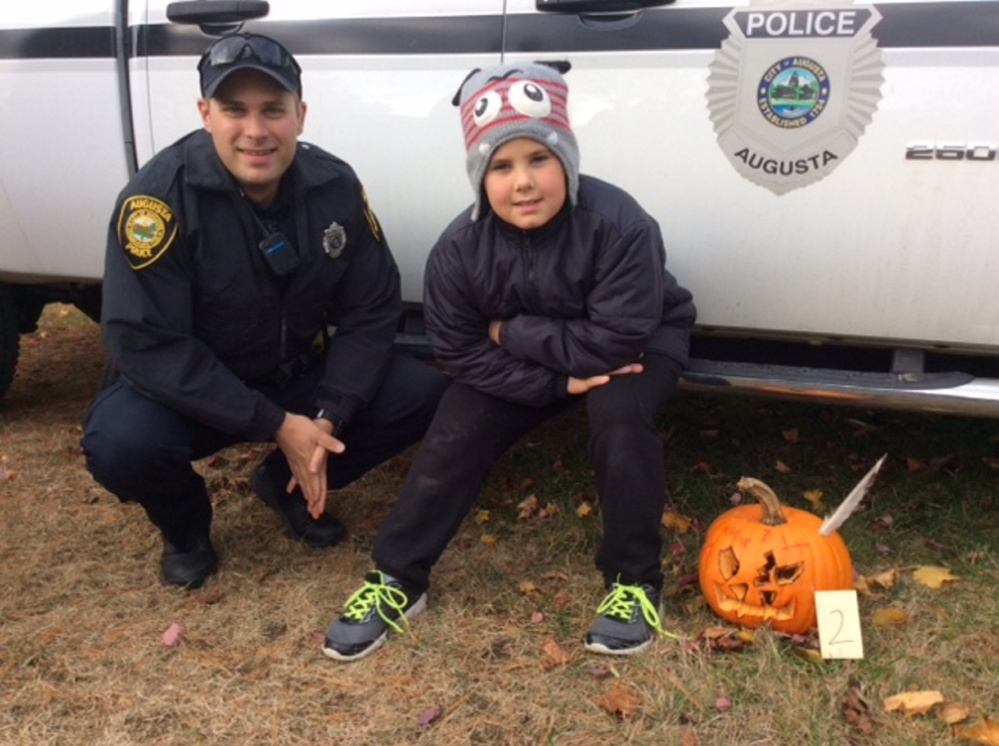 Noah Dow with pumpkin #2 with Officer Jonathan Provisor.