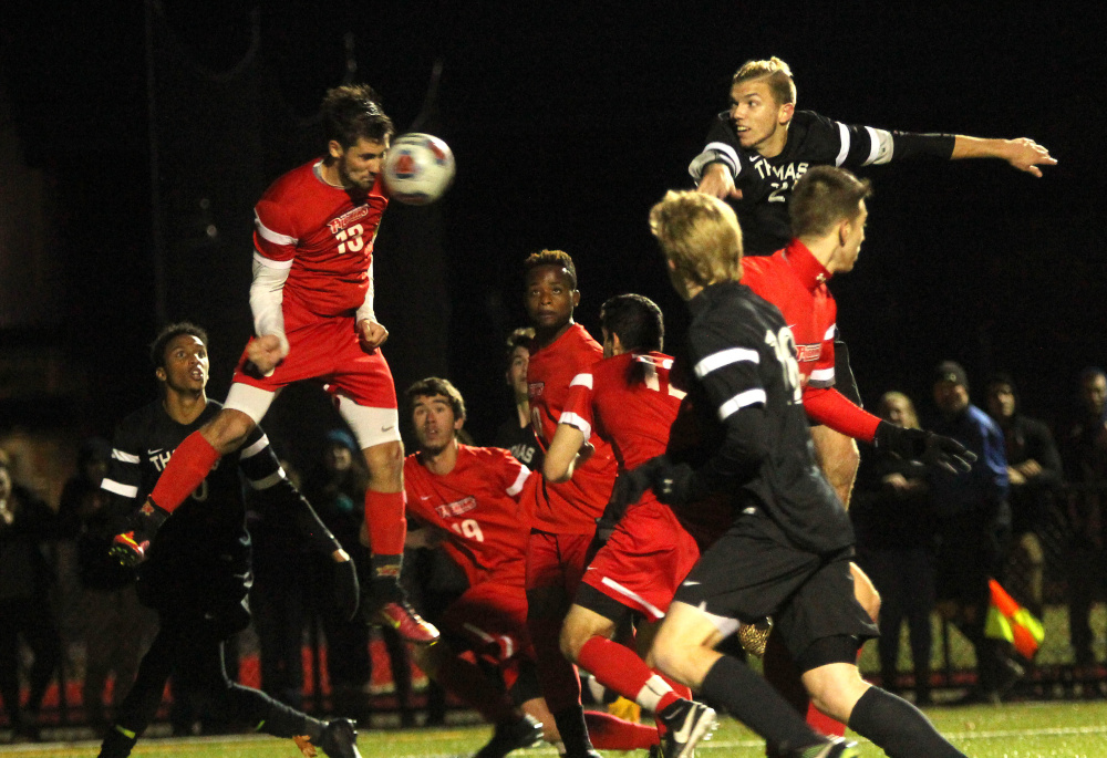 Thomas College's Adam LaBrie, upper right, watches as New England College's Michael Skarbelis heads a free kick away from the goal in the waning moments of regulation during the North Atlantic Conference championship in Waterville on Saturday night.