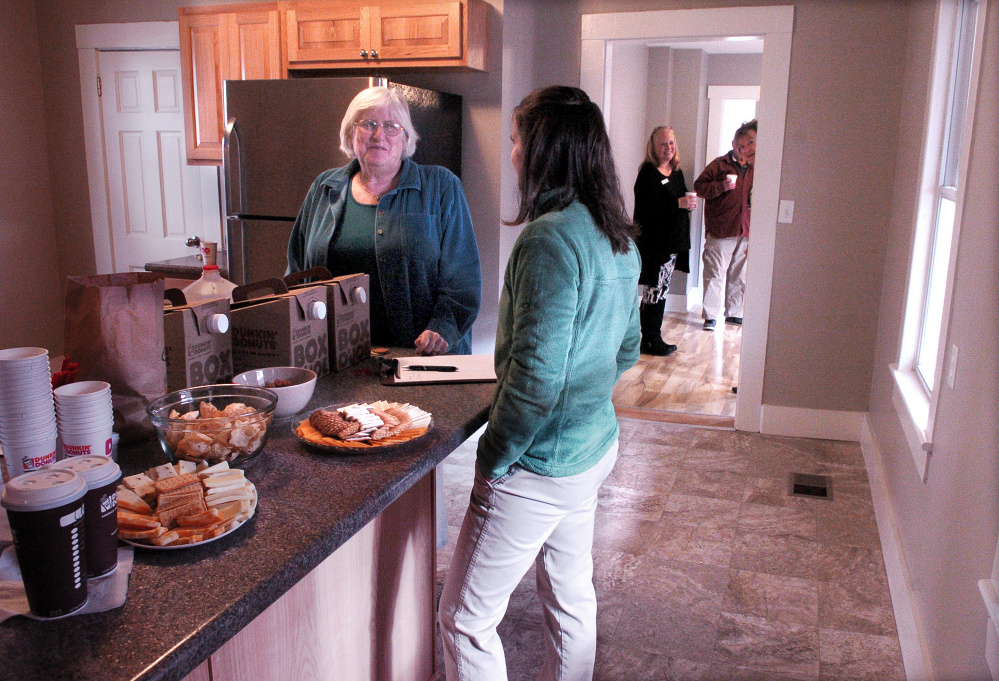 Waterville Community Land Trust board member Ricia Hyde, left, speaks with organization President Ashley Pullen on Sunday during an open house at a home on Water Street in Waterville that the organization renovated and is offering for sale.