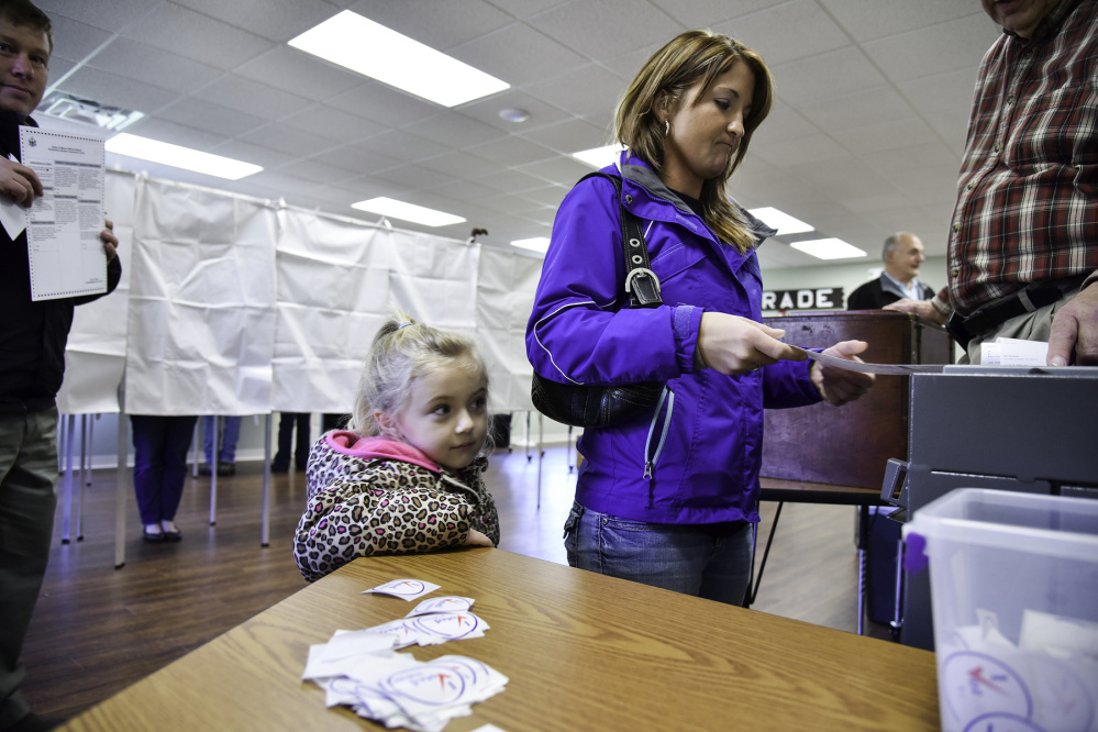 Hailey Jones watches her mother, Tanya, casting a ballot at the Belgrade Town Hall.