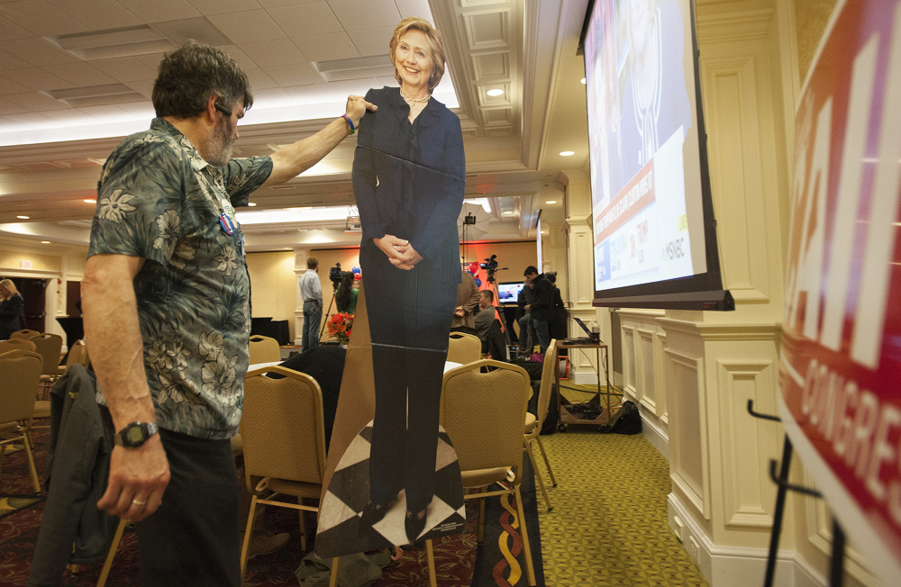 A man who would identify himself only as Harry carries a cardboard cutout of Hillary Clinton into the Hilton Garden Inn ballroom in Bangor Tuesday evening as supporters of Emily Cain started to gather to watch elections results.