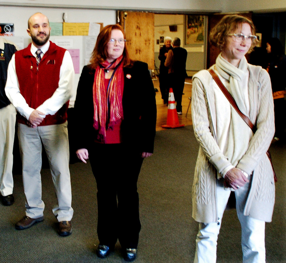 New Waterville city councilors Nick Champagne, left, and Lauren Lessing, right, greet voters Tuesday before the polls close on Election Day. Center is Colleen Madigan, a Democrat who beat Republican Mark Andre in the race for House District 110.