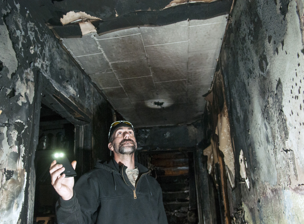 Jeffrey Sansouci shows the location of the smoke alarm that woke him Saturday before a fire destroyed his Randolph home.