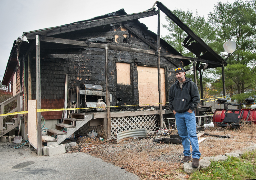 During an interview Wednesday, Jeffrey Sansouci stands outside his Randolph home, which was destroyed by fire Saturday. He credits working smoke detectors for getting him out of the building.