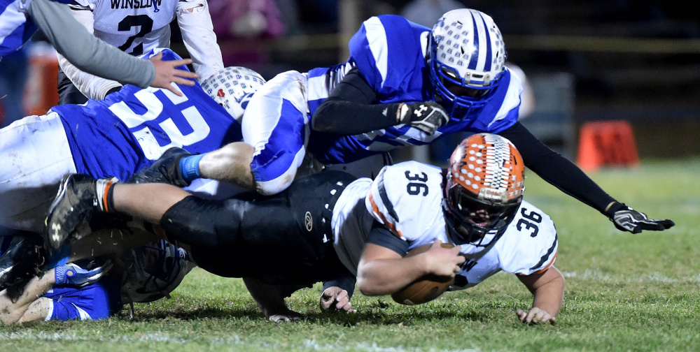 Winslow fullback Kenny Rickard dives for extra yards as Madison defender Max Shibley hauls him down during a Big Ten Conference semifinal game last Friday night at Rudman Field in Madison.