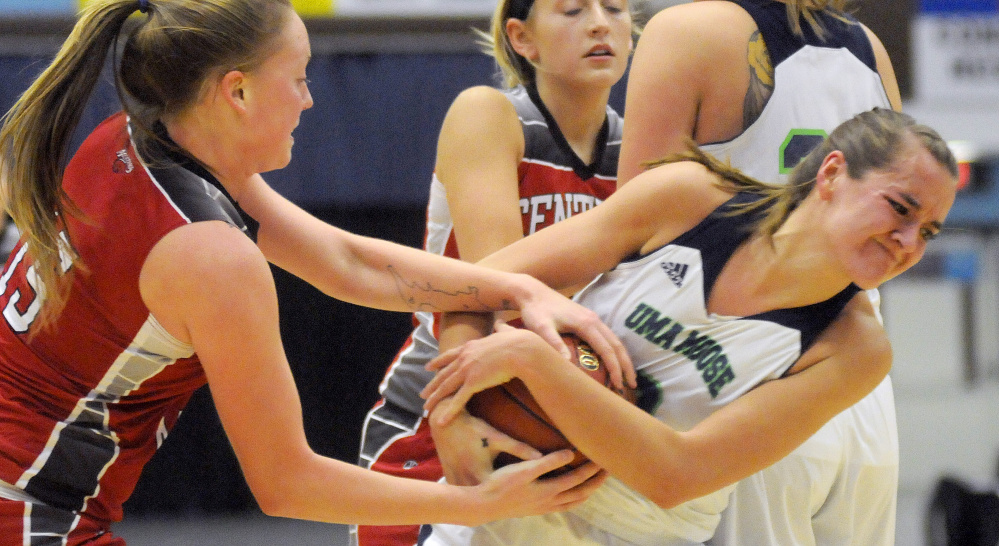 University of Maine at Augusta forward Jamie Plummer, right, wrestles with Central Maine Community College forward Taylor Estes during a game Thursday night at the Augusta Civic Center.