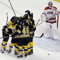 Carolina goalie Cam Ward watches as Bruins players celebrate the game-tying goal by defenseman Torey Krug (47) with seconds to go in the third period of Thursday night's game in Boston. The Bruins won, 2-1, in a shootout.
