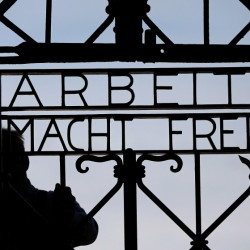 "A  blacksmith prepares a replica of the Dachau camp gate last year with the German slogan for ""Work sets you free."""