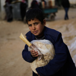 A displaced Syrian boy holds a sandwich and bread bag in the village of Jibreen, south of Aleppo, Syria, on Saturday. Aid agencies say that more than 30,000 people have fled rebel-held eastern neighborhoods of Aleppo.