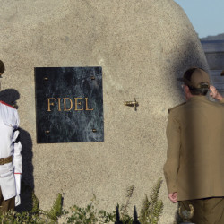 Cuba's President Raul Castro salutes at the tomb of his older brother Fidel, a simple round stone about 15 feet high.
