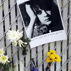 Pictures and flowers adorn a fence Monday near the site of the warehouse fire in Oakland, Calif. The death toll climbed Monday with more bodies still feared buried in the blackened ruins. Associated Press/Marcio Jose Sanchez
