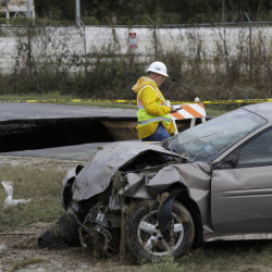 A worker walks past a sinkhole and a car that was pulled from it on Monday in San Antonio. Officials say an off-duty sheriff's deputy has died and two other people hurt when the vehicles plunged into the water-filled sinkhole.