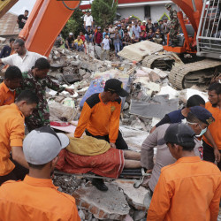 Rescuers recover a victim from the rubble of a collapsed building after an earthquake in Pidie Jaya, Aceh province, Indonesia, on Wednesday. A strong earthquake rocked Indonesia's Aceh province early on Wednesday, killing a large number of people and sparking a frantic rescue effort in the rubble of dozens of collapsed and damaged buildings.