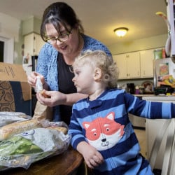 "Emily Griffin of Lisbon Falls unpacks a Blue Apron meal kit as her 2-year-old son, Everett, watches. She uses the delivery service for ""the convenience factor,"" she said. Below, the recipe and ingredients for Smoked Trout Tartines."