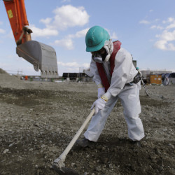 In February a worker levels ground at the crippled Fukushima Dai-ichi nuclear power plant.
