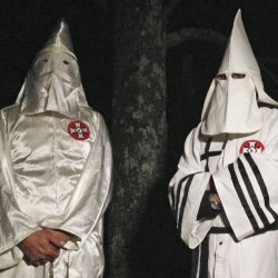 "Two masked Ku Klux Klansmen stand on a muddy dirt road during an interview near Pelham, N.C. The KKK and other white extremist groups are eschewing the term ""white supremacist"" in an attempt to mainstream their racist beliefs."