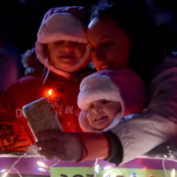 Elizabeth Milcendeau snaps a selfie with her children Aeleyah, 5, and Jaylah, 2, bottom, from the Decal Gymnastics float before the 24th annual Downtown Holiday Stroll in Skowhegan on Friday.