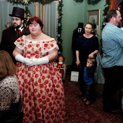 Visitors walk through the Fairfield History House during a holiday tour as Emily Rowden Fournier and Joshua Fournier sing Christmas carols accompanied by Kay Gagnon on the piano while Alexandrea Peterson join in on Sunday.