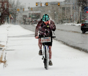 Matt Nurse wore shorts while riding his bike on Main Street in Waterville Monday during the first significant snowfall of the season.