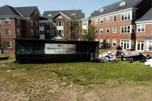 A charred Waste Management dumpster loaded with items from Colby College students is seen May 23 outside the Alfond dormitory on the college campus in Waterville. Three former Colby students on Tuesday pleaded guilty to criminal mischief charges in connection with the fire.