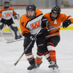 Gardiner/Winslow's Julia Hinkley, left, skates through a check from Brunswick's Jenna Brooks during a girls hockey game Wednesday night at Bonnefond Ice Arena in Kents Hill.
