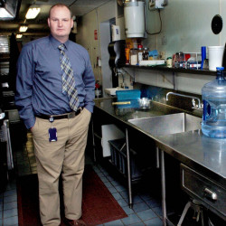 Benton Elementary School Principal Brian Wedge stands beside the school cafeteria's kitchen sink, where exceptionally high levels of lead were detected in October, but further testing has revealed lower levels.